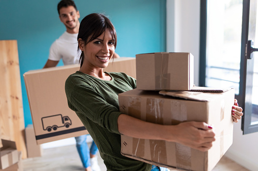 Shot of beautiful young couple holding cardboard boxes while moving to new home. Looking at camera.