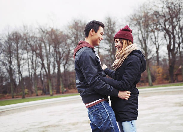 Beautiful young couple in love Handsome young man and beautiful woman standing together looking at each other smiling. Teenage mixed race couple in love in park. cute teen couple stock pictures, royalty-free photos & images
