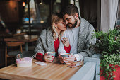 istock Beautiful young couple in warm blankets cuddling at cafe 1086628608