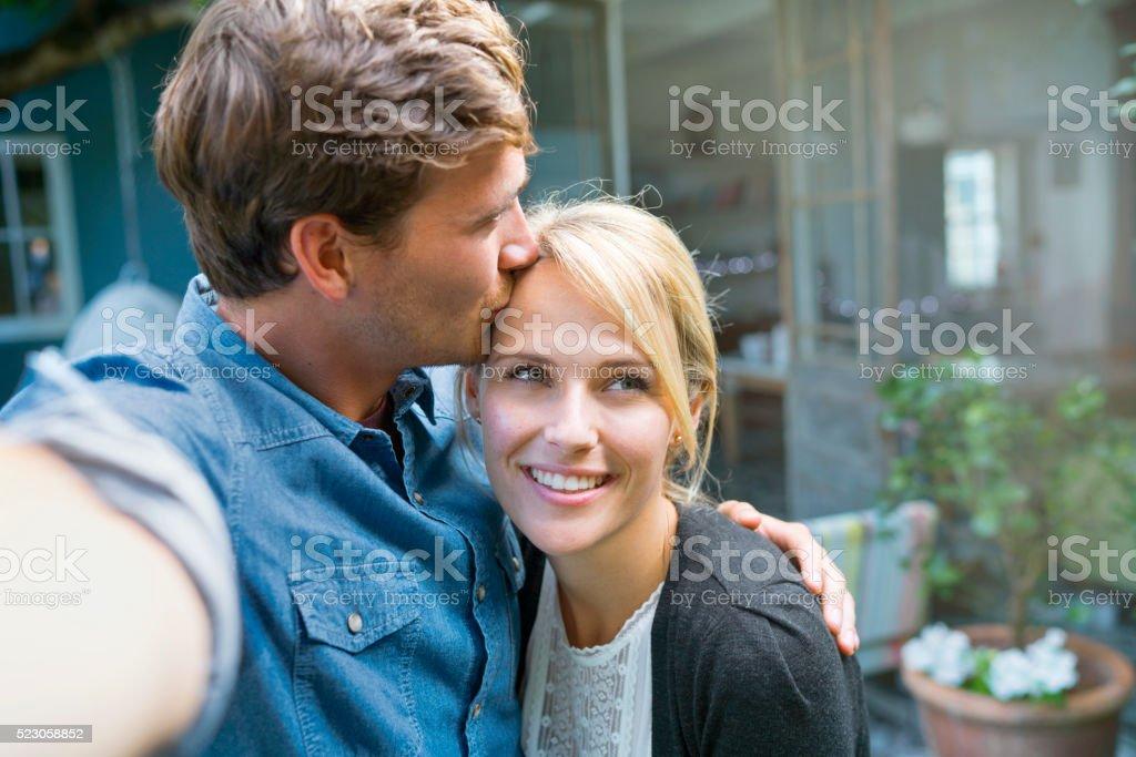 Hermoso Pareja joven beso y hacer selfie en el patio - foto de stock