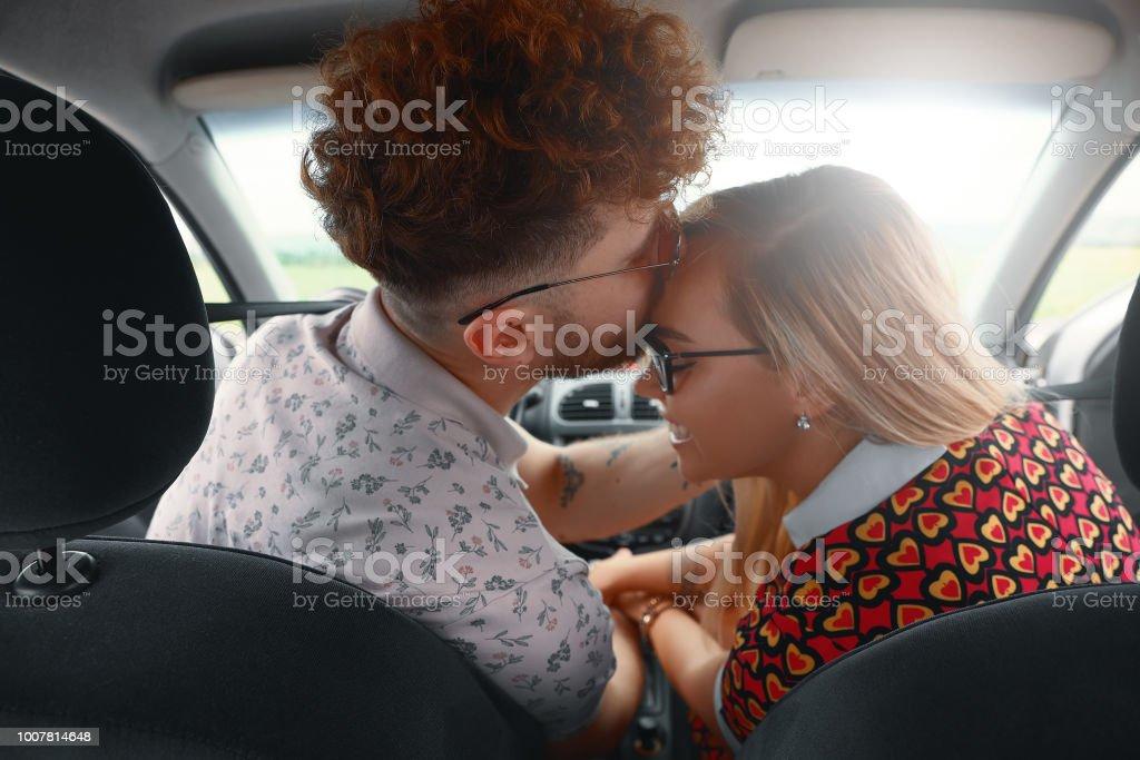 Hermosa joven pareja besándose en el asiento delantero del coche - foto de stock