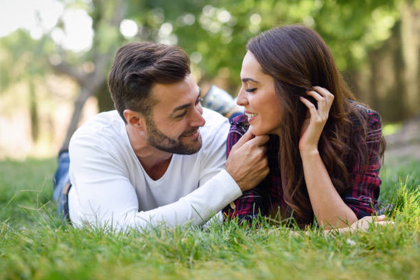 Beautiful young couple laying on grass in an urban park. stock photo