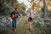 Beautiful young couple playing music together while walking in the forest with the guitar and accordion. in the Mallorca forest landscape. Slightly grain added.