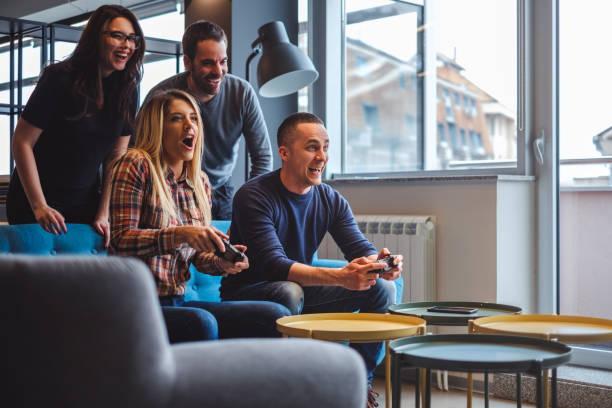 Hermosa joven pareja jugar video juegos con amigos - foto de stock