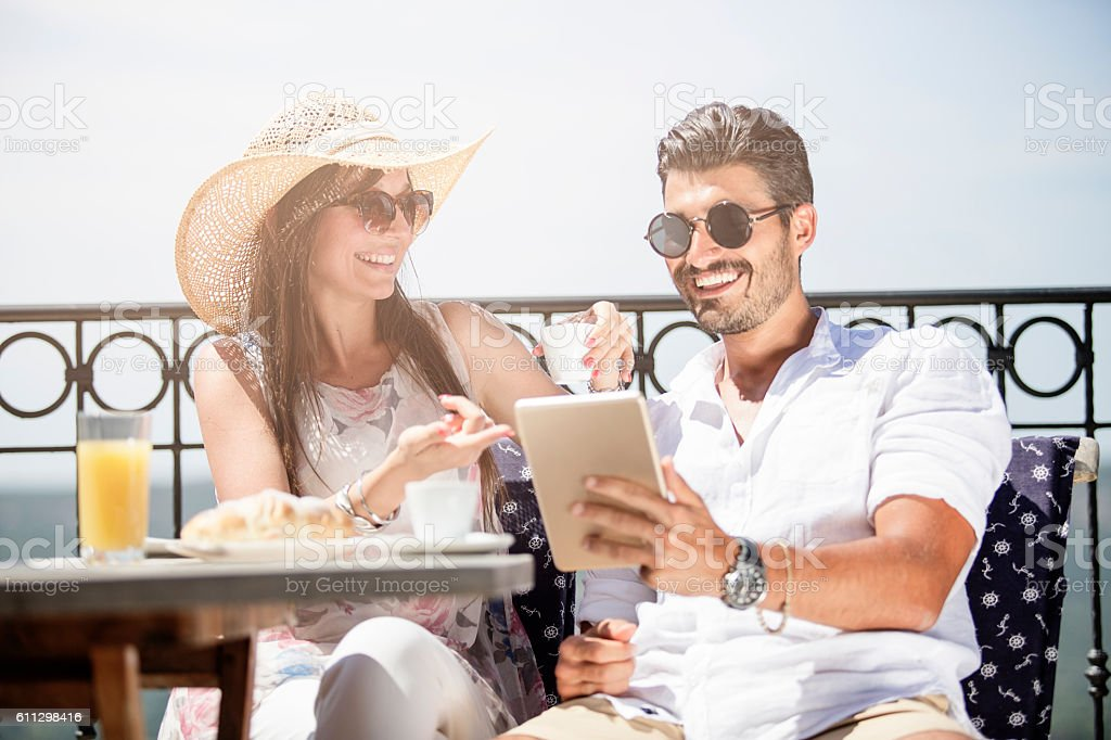 Beautiful young couple reading the news at tablet stock photo