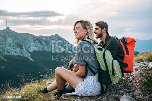young couple of hikers enjoying the beautiful nature from high above