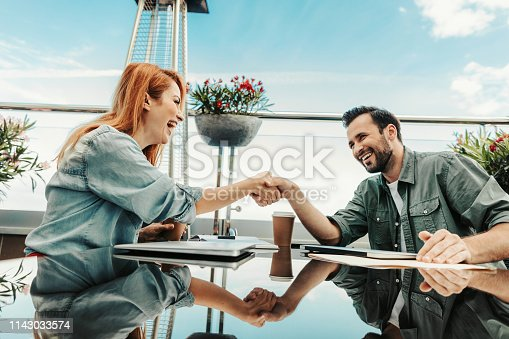 Lovely meeting. Cheerful lady making a deal with bearded man at outdoor cafe. They sitting at the table with laptops, cup of coffee and notebook