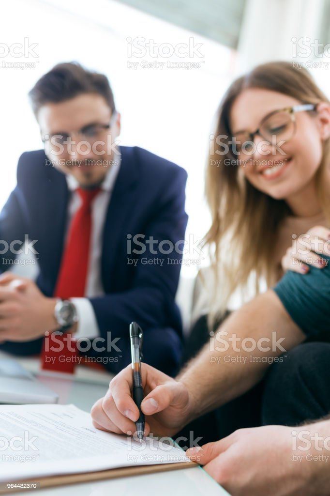 Beautiful young couple signing financial contract in the office. - Royalty-free Adult Stock Photo
