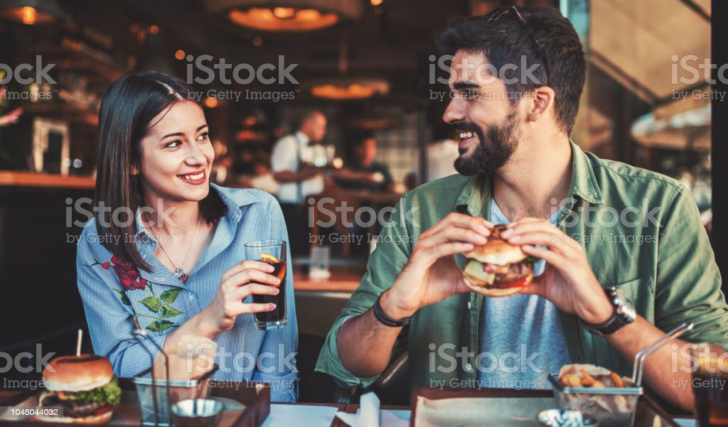 Beautiful young couple sitting in a cafe, having breakfast. Love, dating, food, lifestyle concept stock photo