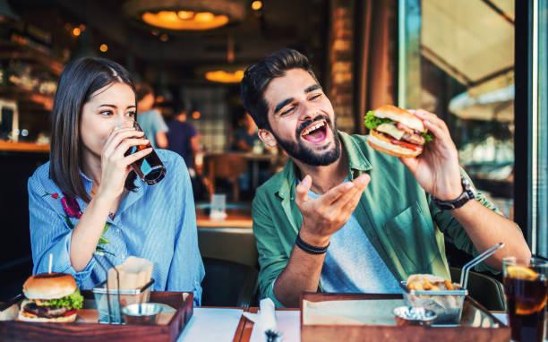Schönes junges Paar sitzt in einem Café, frühstücken. Love, Dating, Food, Lifestyle-Konzept – Foto