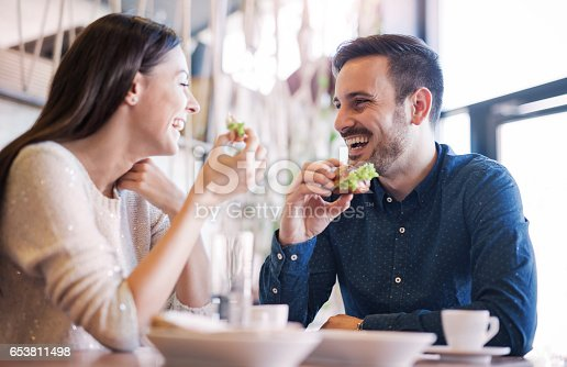 istock Beautiful young couple sitting in a cafe, having breakfast. Love, food, lifestyle 653811498