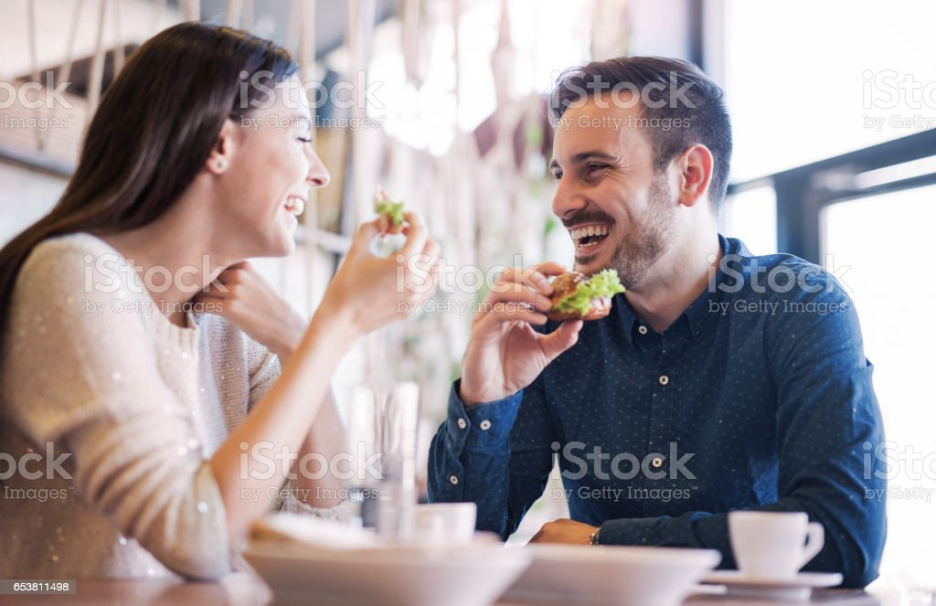 Beautiful young couple sitting in a cafe, having breakfast. Love, food, lifestyle stock photo