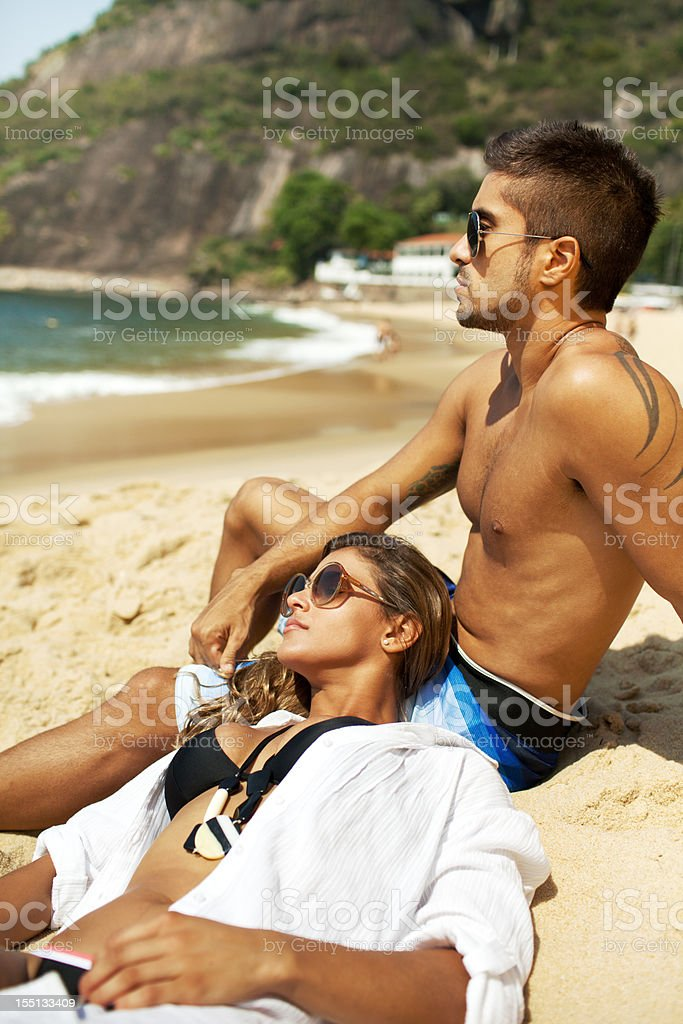 Beautiful young couple sitting on the beach enjoying sunny day. royalty-free stock photo