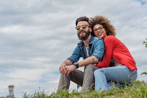 beautiful young couple smiling at the park - love at first sight stock photos and pictures