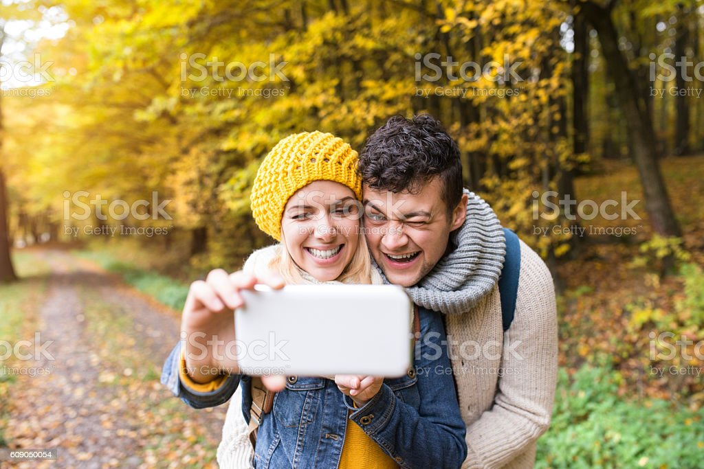 Beautiful young couple taking selfie in autumn forest