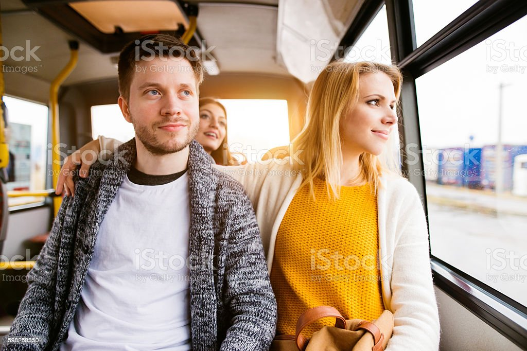 Beautiful young couple traveling by bus, having fun stock photo