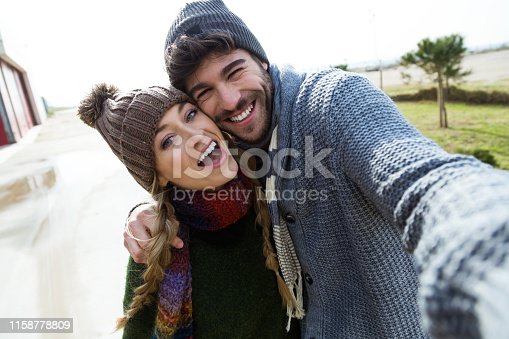 Portrait of beautiful young couple using mobile phone in a cold winter on the beach.