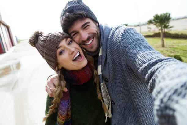 Schönes junges Paar mit Handy in einem kalten Winter am Strand. – Foto