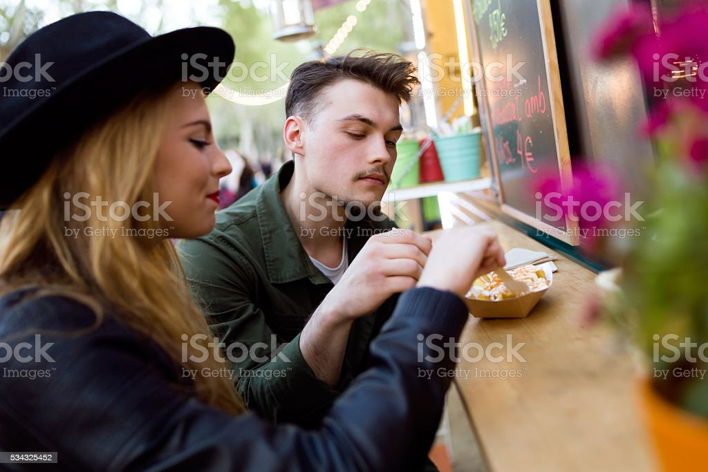 Beautiful young couple visiting eat market in the street. stock photo