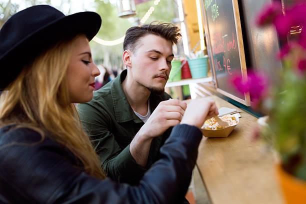 wunderschöne junges paar sie essen in die markt street ab. - streetfood stock-fotos und bilder