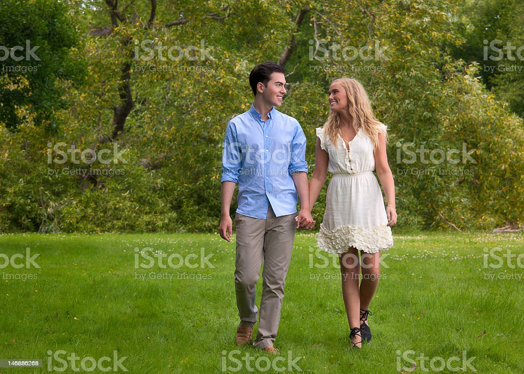 Beautiful young couple walking in the park at Summer royalty-free stock photo