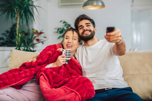 beautiful young couple watching tv in living room. - date night stock pictures, royalty-free photos & images
