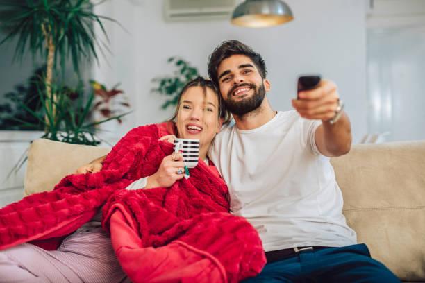hermosa joven pareja viendo tv en la sala de estar. - date night fotografías e imágenes de stock