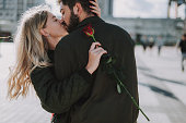 istock Beautiful young couple with flower hugging and kissing on the street 1086628538