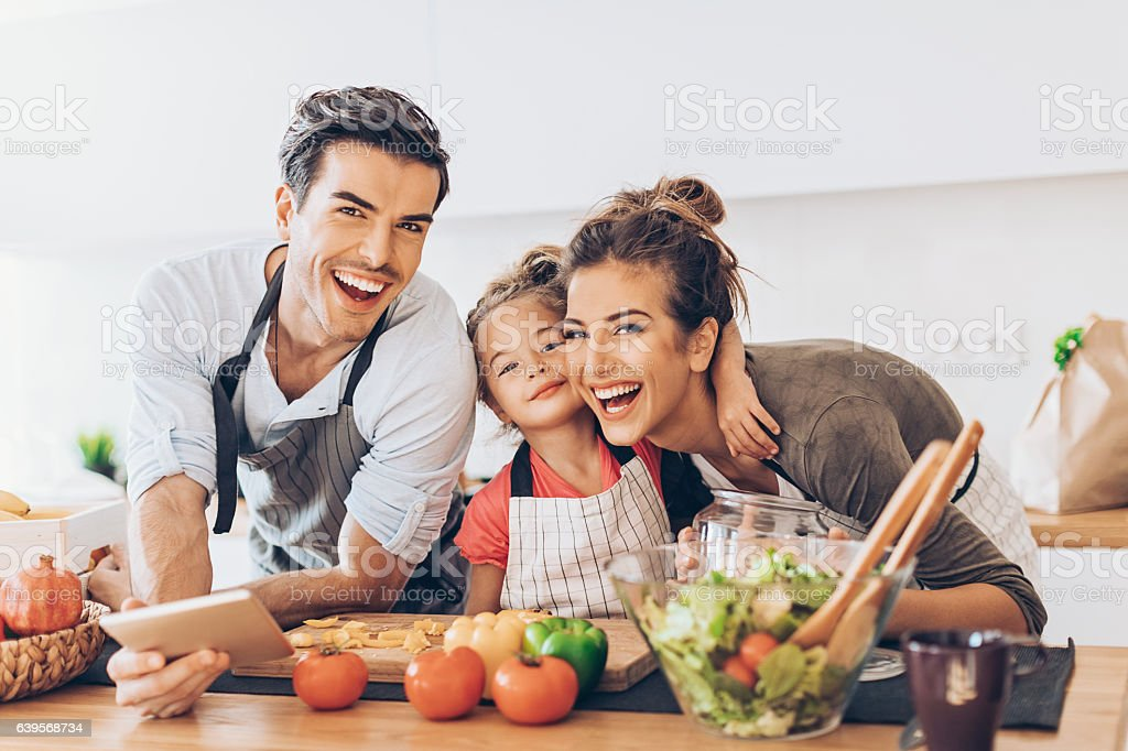 Beautiful young couple with small girl in the kitchen – Foto