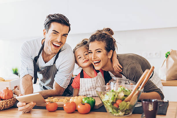 beautiful young couple with small girl in the kitchen - kids cooking stock photos and pictures