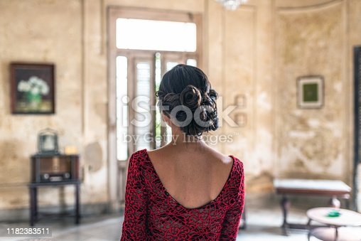 rear view on beautiful young cuban woman in red dress in old house in Havana