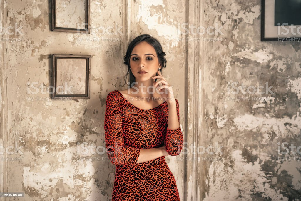 beautiful young cuban woman in red dress in old house stock photo