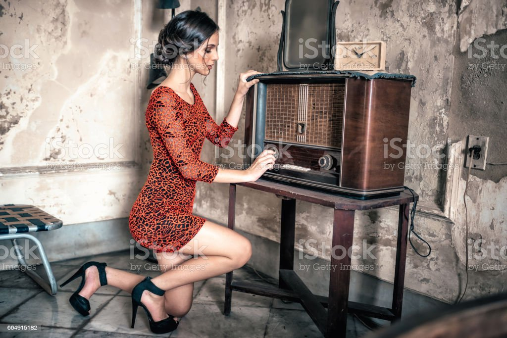 beautiful young cuban woman in red dress switch on vintage radio foto stock royalty-free