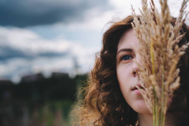 美麗的年輕卷髮紅頭髮的女孩在森林的背景 - 殺球 個照片及圖片檔
