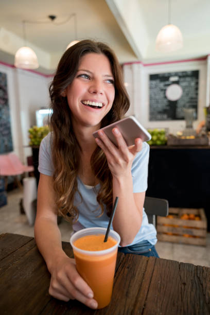 Beautiful young customer talking on her smartphone using the speakerphone looking very happy while enjoying a fresh juice at a juice bar stock photo