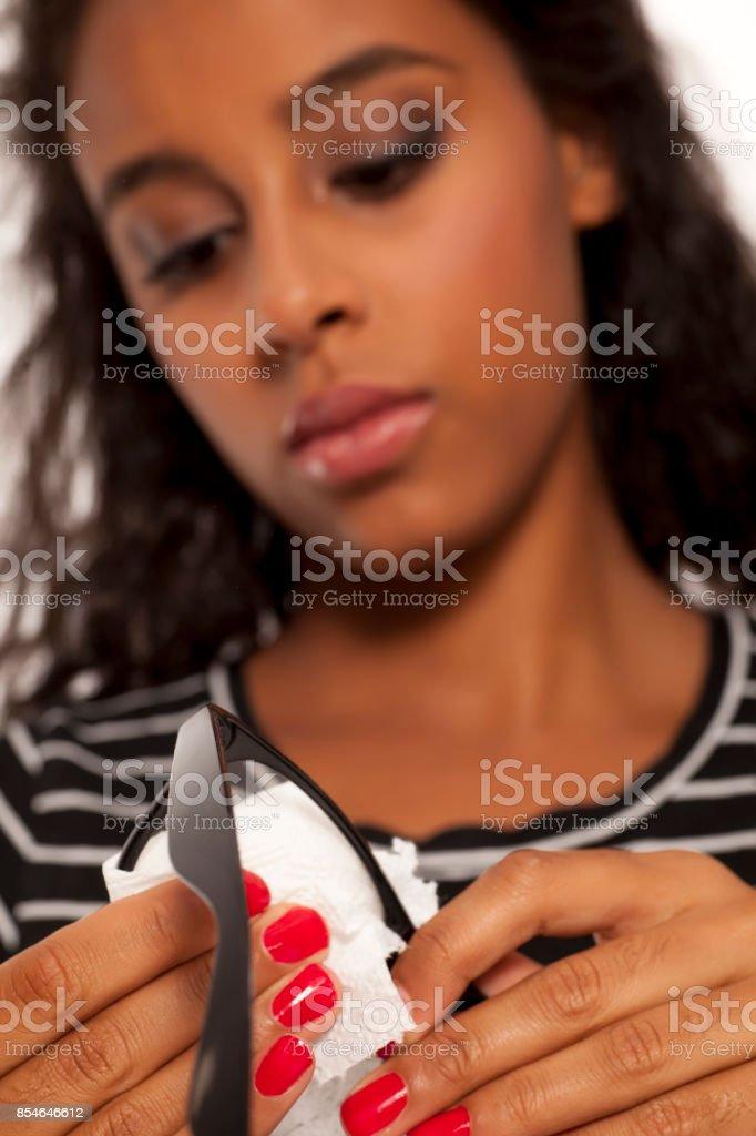 belle jeune femme peau sombre nettoyer ses lunettes de vue - Photo
