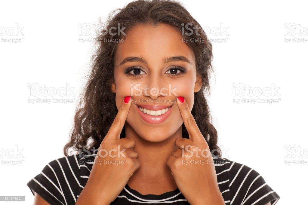 belle jeune noir peau femme Famn son sourire avec ses doigts - Photo