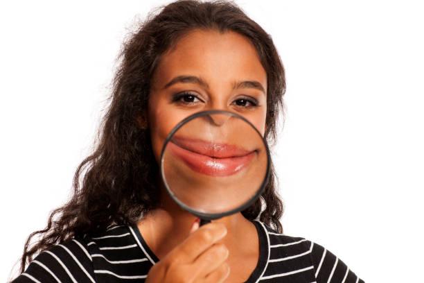 Belle jeune femme peau sombre tenant un verre grossissant devant sa bouche - Photo