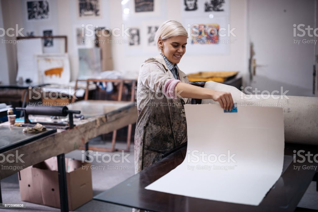 Beautiful young determined entrepreneur working in printing shop stock photo