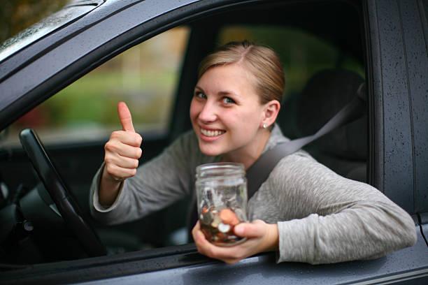 Schöne junge Fahrer speichern Münzen Geld für gas – Foto