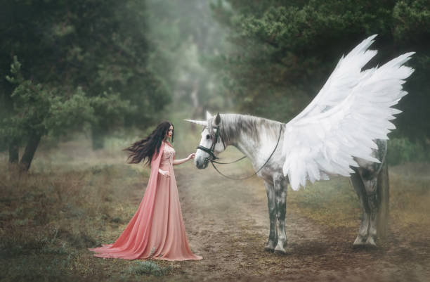 beautiful, young elf, walking with a unicorn in the forest she is dressed in a long orange dress with a cloak. the plume beautifully waves in the wind. artistic photography - pegasus stock photos and pictures