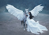 istock Beautiful, young elf, walking with a unicorn. She is wearing an incredible light, white dress. Art hotography 917914552