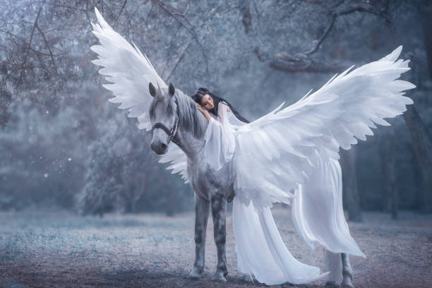beautiful, young elf, walking with a unicorn. she is wearing an incredible light, white dress. the girl lies on the horse. sleeping beauty. artistic photography - skrzydło samolotu zdjęcia i obrazy z banku zdjęć