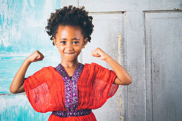 Beautiful young Ethiopian girl in traditional clothing, showing strength stock photo