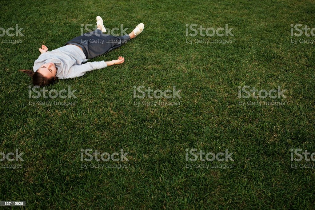 Beautiful young european woman lays down on grass and rests stock photo