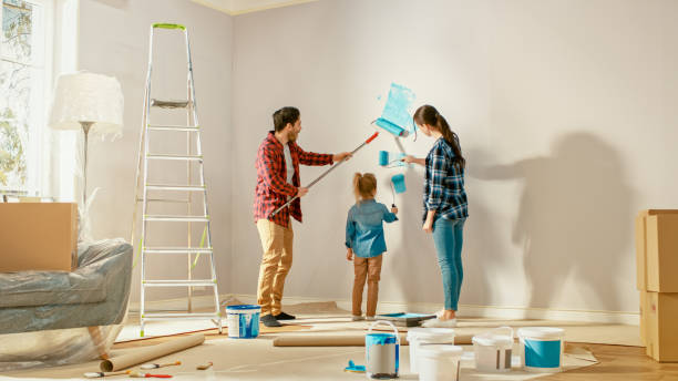 beautiful young family are showing how to paint walls to their adorable small daughter. they paint with rollers that are covered in light blue paint. room renovations at home. - zrób to sam zdjęcia i obrazy z banku zdjęć