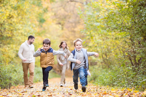 Beautiful young family on a walk in autumn forest.