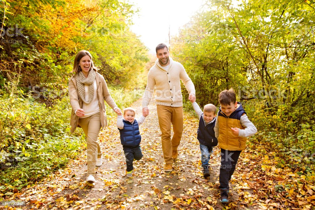Beautiful young family on a walk in autumn forest. stock photo