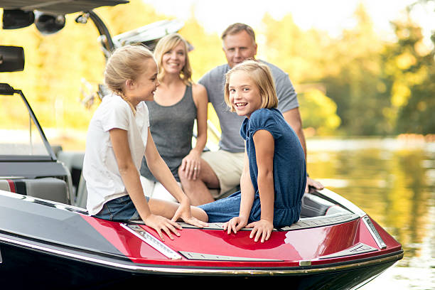 Beautiful young family sits in their ski boat - Photo