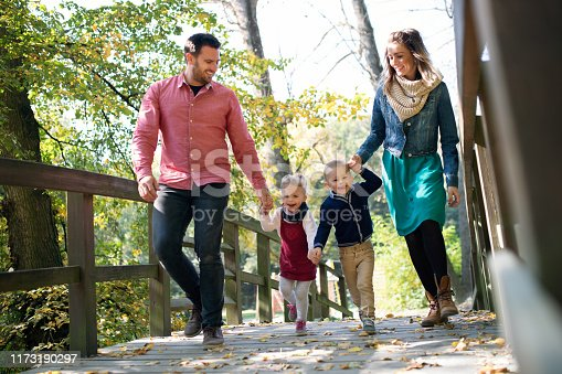 A beautiful young family with small twins on a walk in autumn forest, holding hands.